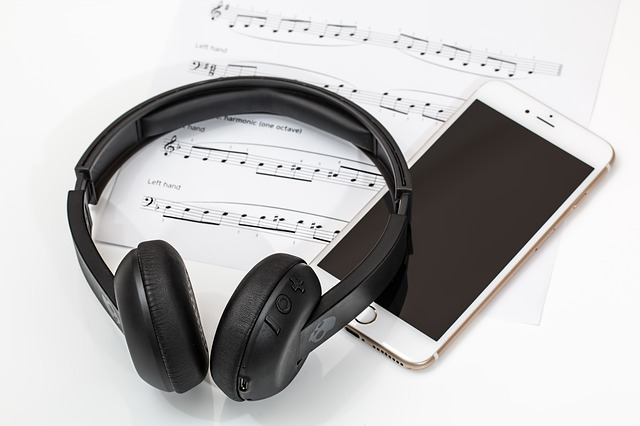 Photograph of headphones, sheet music and smart phone